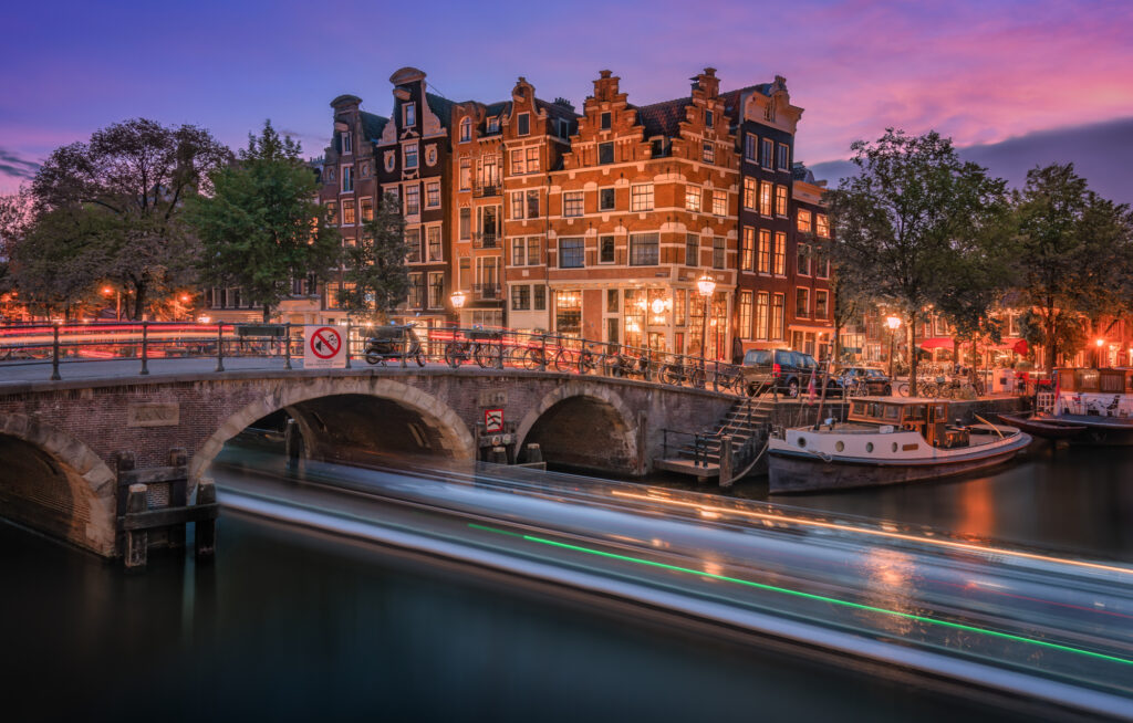Colorful long exposure capture of a boat passing on the Amsterdam Canals